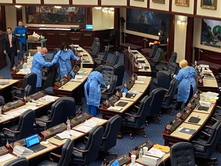 people in protective clear clean desks in Florida House
