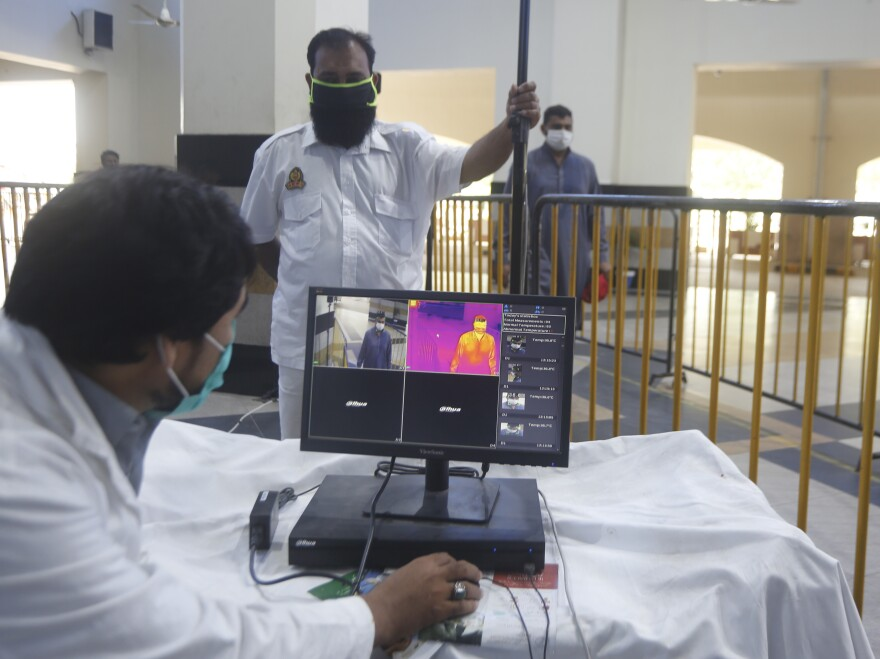 Railway staff in Pakistan use a thermal scanner to check visitors for coronavirus symptoms. Pakistan was one of the nine countries added to the U.N.'s new aid plan.
