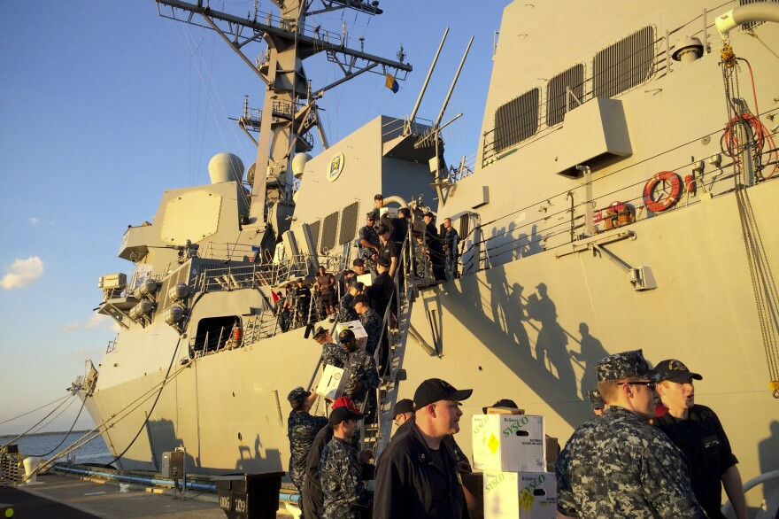 Crew members of the U.S. Navy destroyer USS Jason Dunham load supplies while docked in Guantanamo Bay, Cuba, earlier this year. The U.S. and Cuba have restored diplomatic relations, but the U.S. says it remains committed to keeping the base.