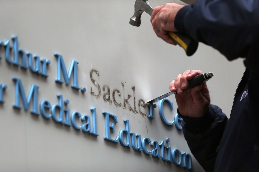 Tufts employee Gabe Ryan removes letters from signage featuring the Sackler family name at the Tufts building in Boston on Dec. 5, 2019. Tufts University was the first major university to strip the Sackler name from buildings and programs.
