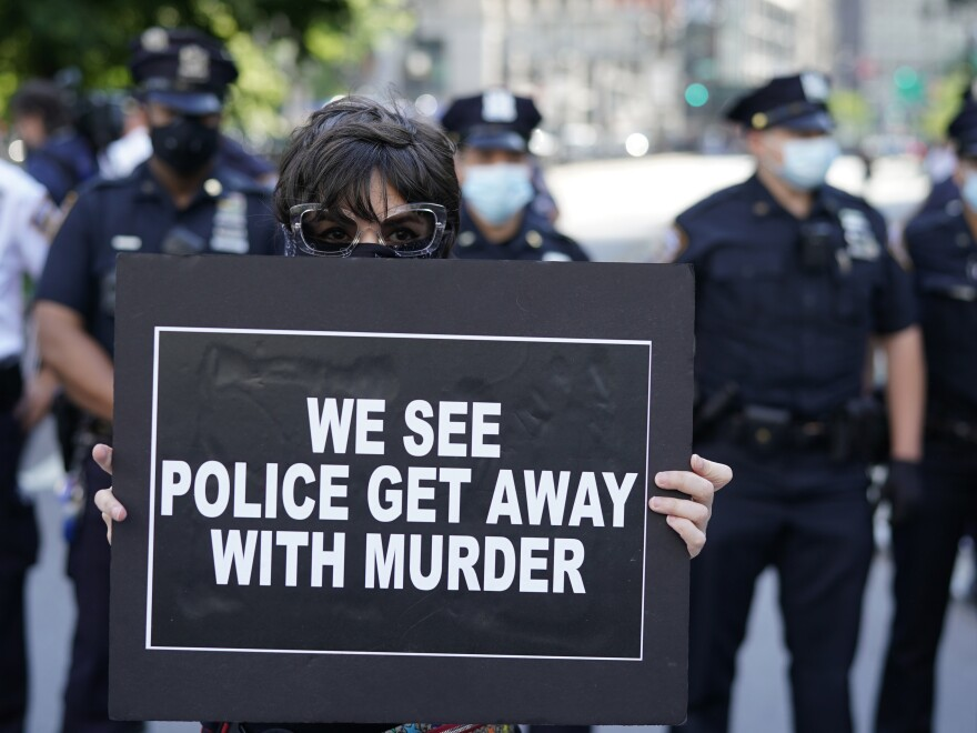 New York City Police officers stand behind a protester during a vigil at Foley Square in New York last month.