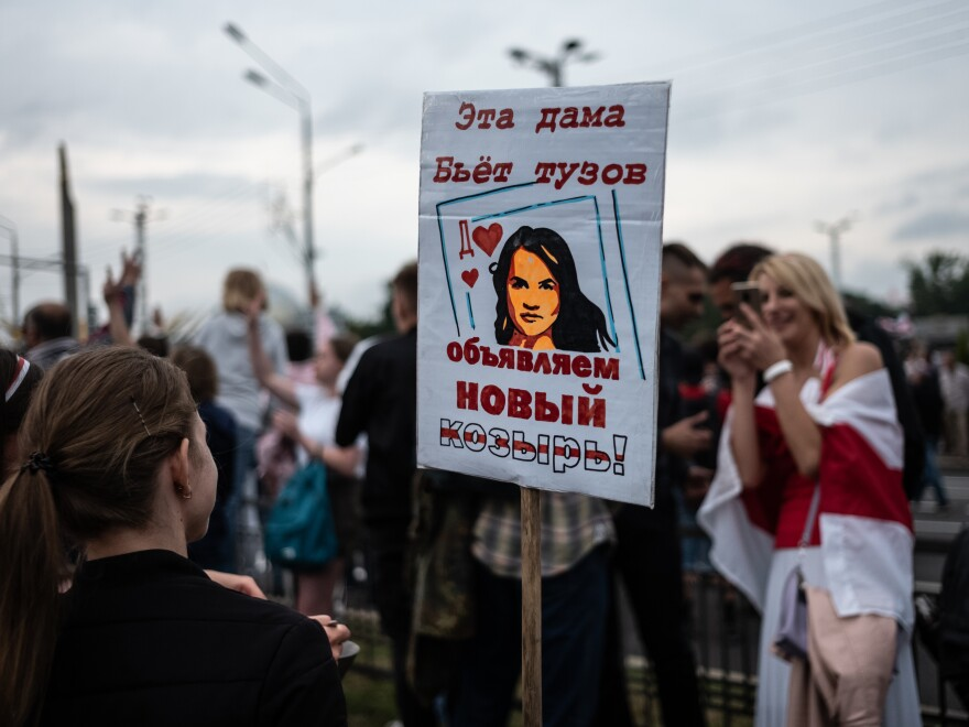 Anti-government protesters hold a sign with a picture depicting Belarusian opposition leader Svetlana Tikhanovskaya as a card that trumps an ace on Aug. 23 in Minsk.