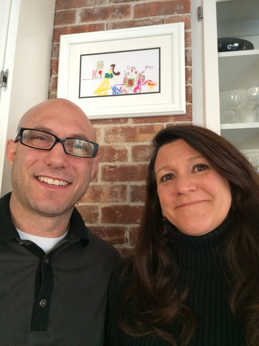 """Jeremy Richman and Jennifer Hensel pose at their home with artwork from their daughter, Avielle. Richman says his daughter """"was very happy and wanted everyone else to be, too."""""""