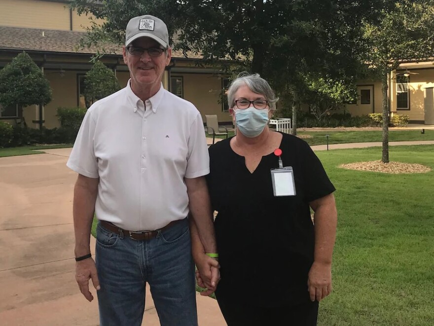 Mary Daniel stands in a mask and scrubs next to her husband Steve after she accepted a job as a dishwasher at his assisted-living facility.
