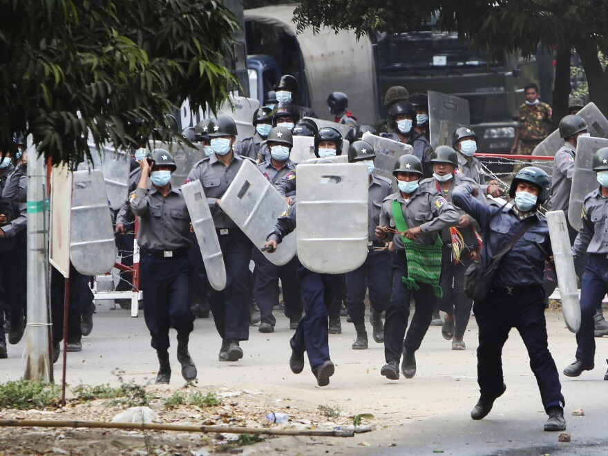 Police charge forward to disperse protesters in Mandalay, Myanmar, on Saturday. Security forces  ratcheted up their pressure against anti-coup protesters, using water cannons, tear gas, slingshots and rubber bullets.