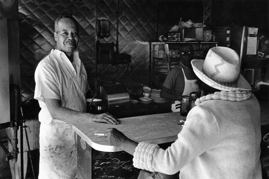 Dawoud Bey's <em>Mr. Moore's Bar-B-Que, 125th Street</em> shows someone actually enjoying their work.