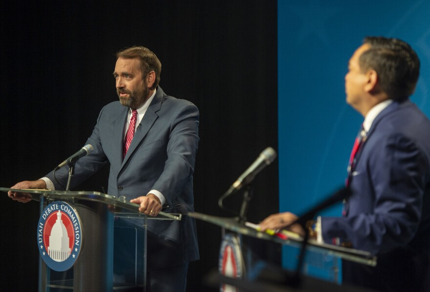 Photo of two men behind podiums on a stage