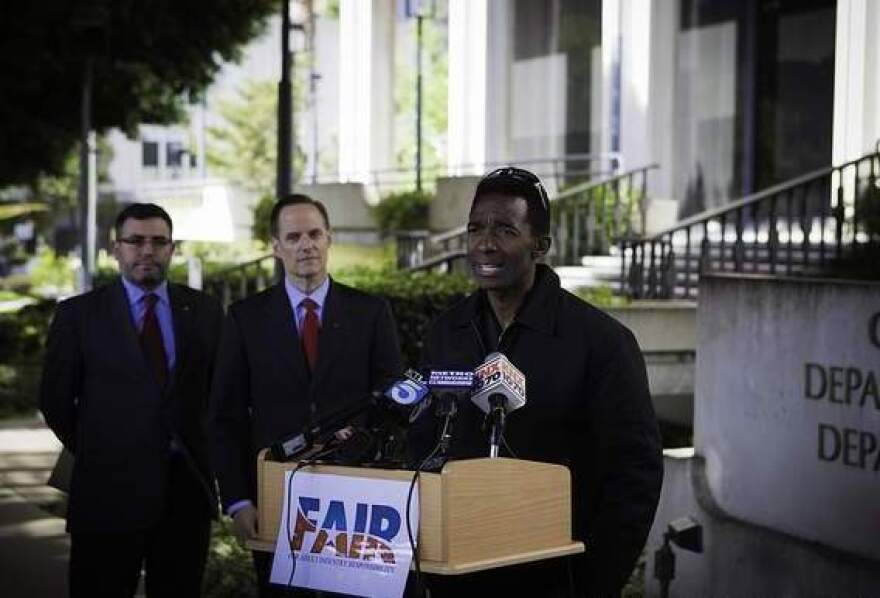 Former adult film star Darren James speaks about the policy of requiring adult film actors to use condoms, as Michael Weinstein (middle), head of the AIDS Healthcare Foundation, looks on.