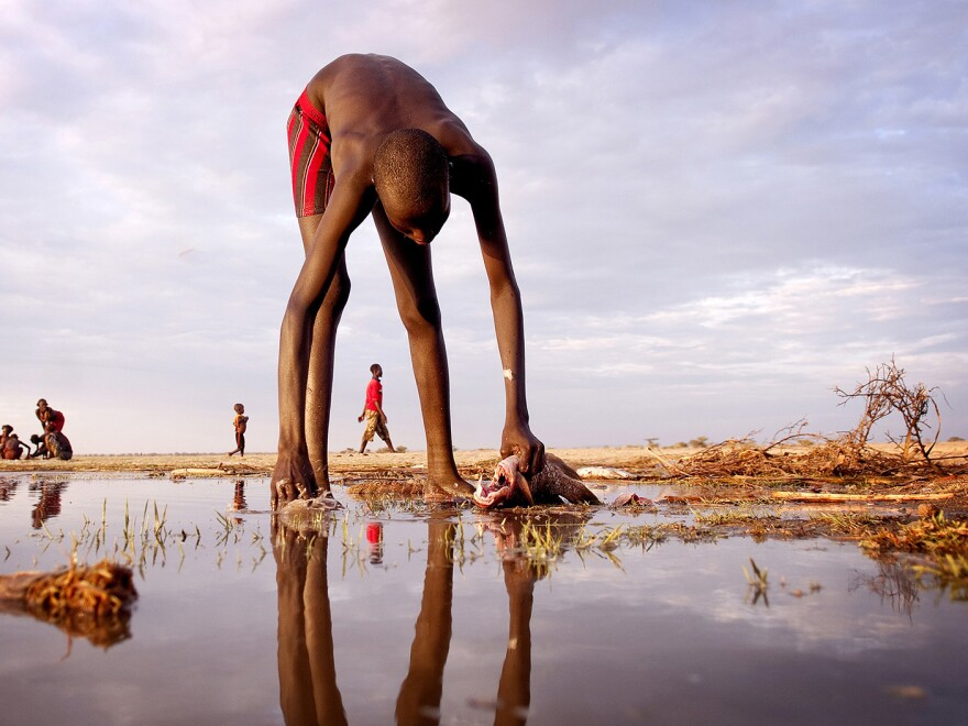 A Daasanach fisherman guts and cleans a fish on the eastern shore of Lake Turkana near the border of Ethiopia and Kenya.