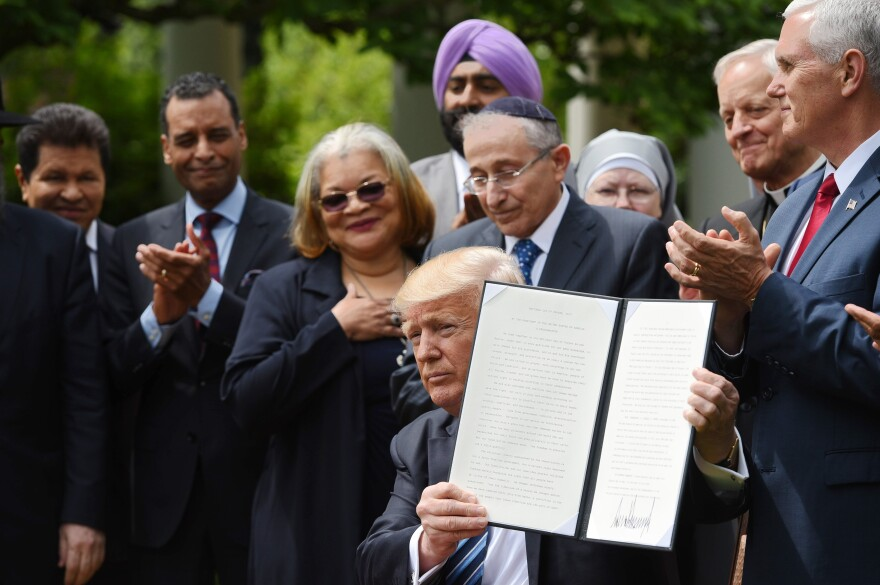 President Trump holds up a proclamation after signing it in the Rose Garden of the White House on Thursday. Trump said he was making it easier for churches and religious groups to take part in politics without risk of losing their tax-exempt status.