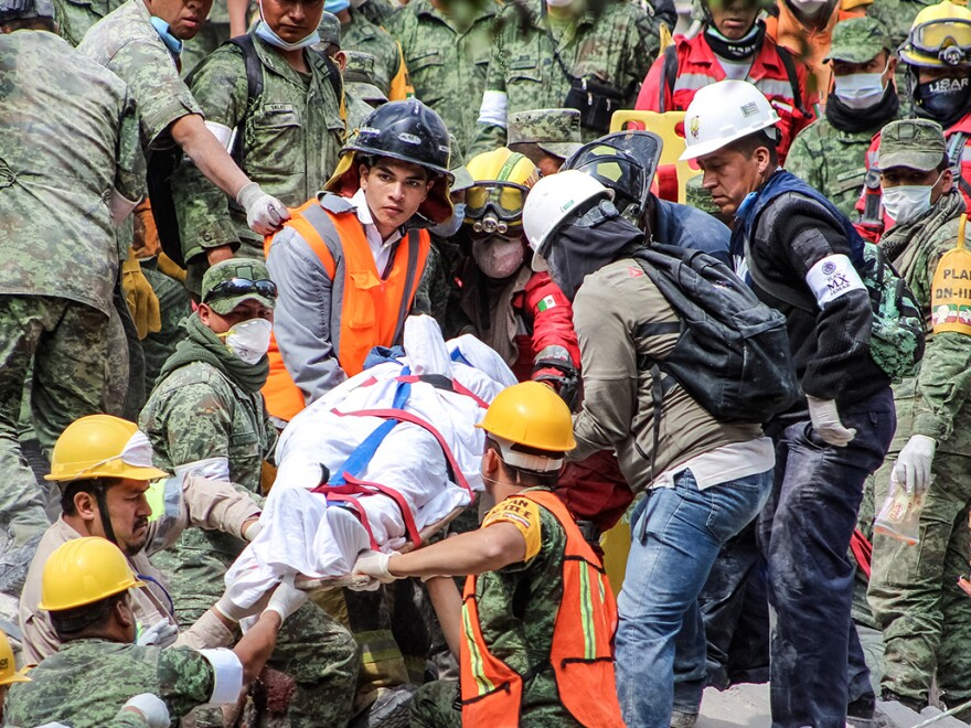 Search and rescue groups carry a body through the rubble of a collapsed apartment building in Mexico City on Wednesday.