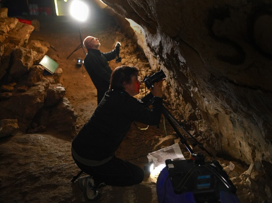 Researchers work in the cave where the conch shell was found.