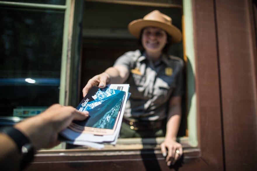 A ranger hands a visitor park information at one of Glacier National Park's entrances.
