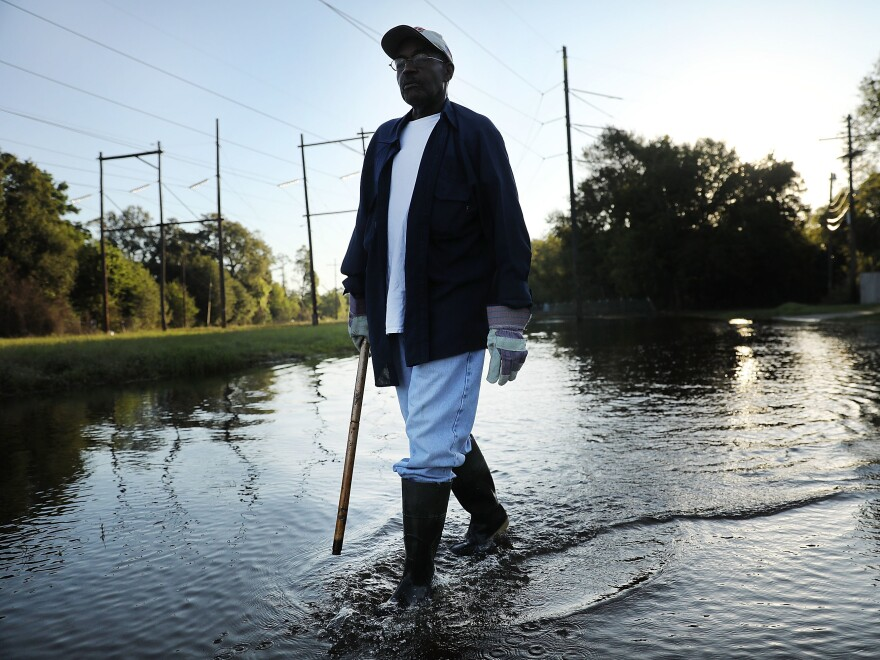 Paul Morris checks on neighbors homes in a flooded district of Orange as Texas slowly moves toward recovery from the devastation of Hurricane Harvey.