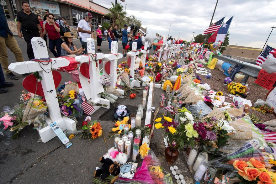 People leave flowers at a makeshift memorial for shooting victims at the Cielo Vista Mall Walmart, in El Paso, Texas.