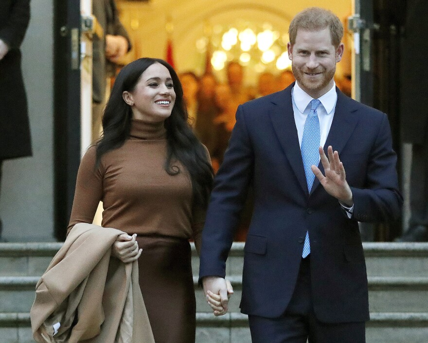 Meghan Markle and Prince Harry walking down steps, smiling, hand in hand.