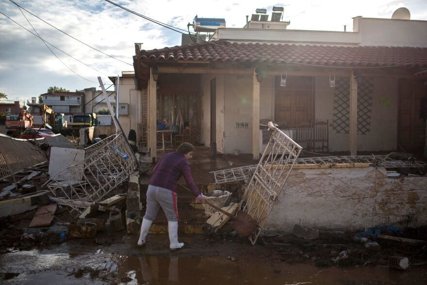 "Flash floods killed at least 20 people in Greece, in a storm some were calling a ""medicane."" A woman cleans mud in front of a house in the town of Mandra, northwest of Athens, on Friday."