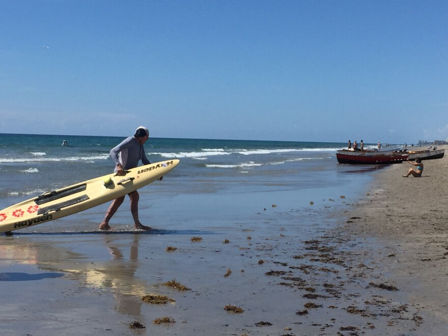 Tom Hogan, 82, drags his board onto shore after completing his event.