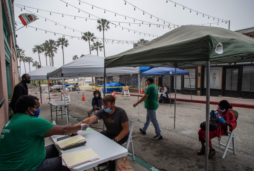 Homeless people wait to be checked-in to a hotel room in Venice Beach, Calif., on April 26. The NGO St. Joseph Center is providing Hotel rooms to the homeless people at risk or infected with COVID-19, through Project Roomkey of the City of Los Angeles.
