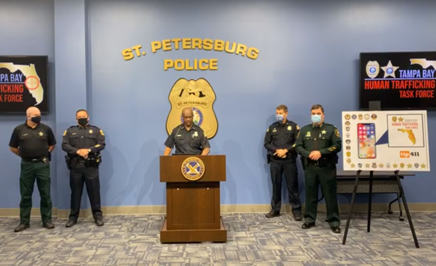 Four uniformed police officers, including Chief Anthony Holloway, stand around a podium at police headquarters to announce the app. A poster board to their left shows a photo of a smartphone with the app installed.