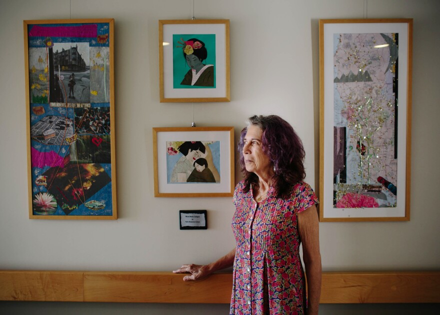 Kyle Cohen, 65, stands in the hallway of the Long Beach Senior Arts Colony in Long Beach, Calif., with a few of her art pieces hanging on display. She was on a waiting list for two years before she got her current apartment.