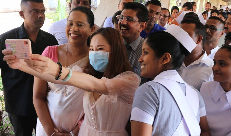 A recovered coronavirus patient takes a selfie before being discharged from a hospital in Sri Lanka. Researchers are trying to determine whether having a case of COVID-19 will give you immunity.