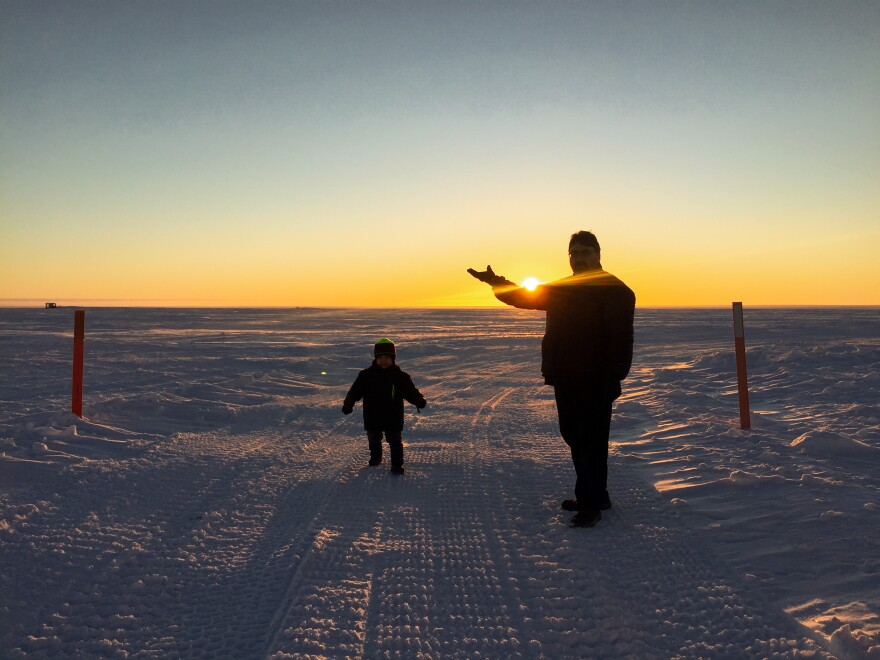 Robin Mongoyak and his young son enjoy the sunshine out on the southern edge of Utqiaġvik.