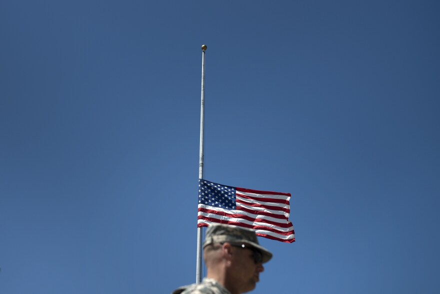 A soldier walks past a flag at half staff before a memorial service at Fort Hood on April 9, 2014 in Texas.