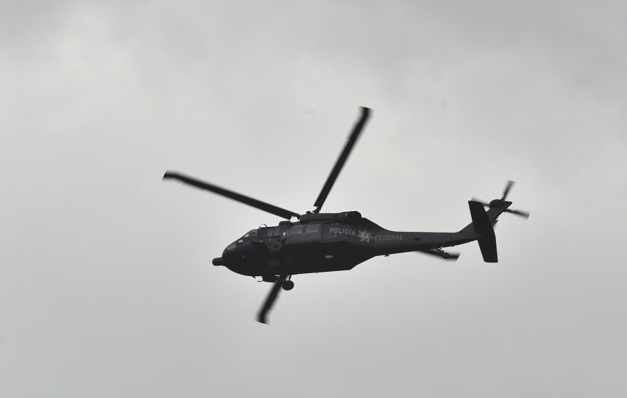 """A federal police Black Hawk helicopter flies over a house at the end of a tunnel through which drug lord Joaquin """"El Chapo"""" Guzman could have escaped from Mexico's Altiplano prison."""