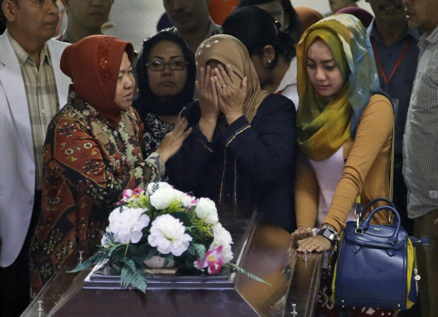 A relative weeps during the handover of the body of Hayati Lutfiah Hamid, one of the victims of AirAsia Flight 8501, to her family at the police hospital in Surabaya, East Java, Indonesia, on Thursday.