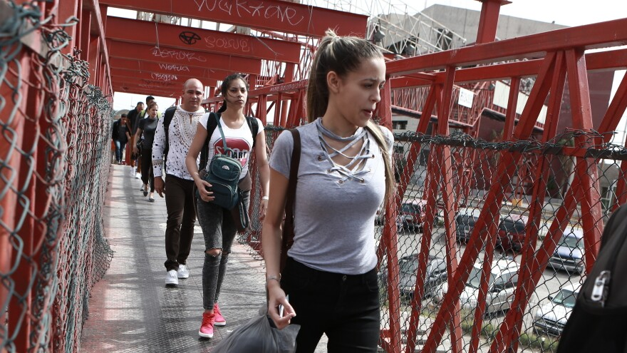 "Cuban migrants cross a bridge in Mexico to be processed as asylum-seekers in the U.S. The labor union representing asylum officers claims the policy formally known as the Migrant Protection Protocols is a ""widespread violation"" of international and domestic law."
