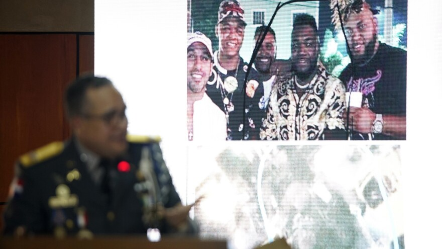 Ney Aldrin Bautista Almonte, director of the Dominican Republic's national police, projects a photograph of David Ortiz (second from right) taken on the night he was shot in Santo Domingo. Officials say a gunman shot Ortiz after mistaking him for Sixto David Fernández, not pictured.