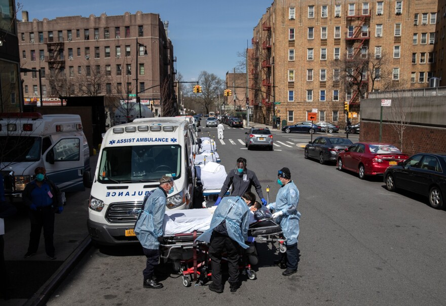 Paramedics and hospital workers prepare to lift a COVID-19 patient onto a hospital stretcher outside the Montefiore Medical Center Moses Campus, the Bronx, Tuesday, April 07, 2020, New York City.