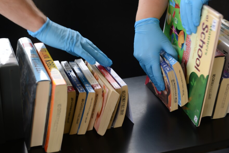 Picture of hands wearing blue sanitary gloves to handle library books
