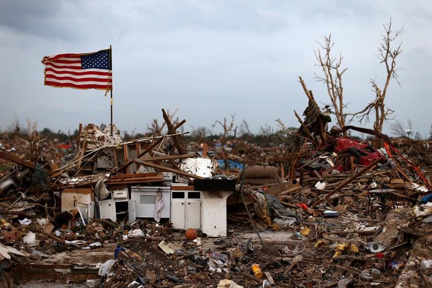 An American flag flies over the rubble of a destroyed neighborhood on May 24 in Moore, Okla.
