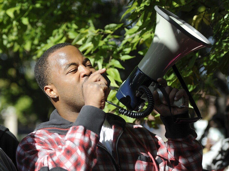 Rashad Turner, founder of the St. Paul chapter of Black Lives Matter, speaks to supporters before they begin a march against police brutality in St. Paul, Minn., on Oct. 4 2015.