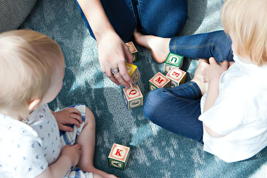Two children are sitting on a blue rug playing with colorful alphabet blocks.