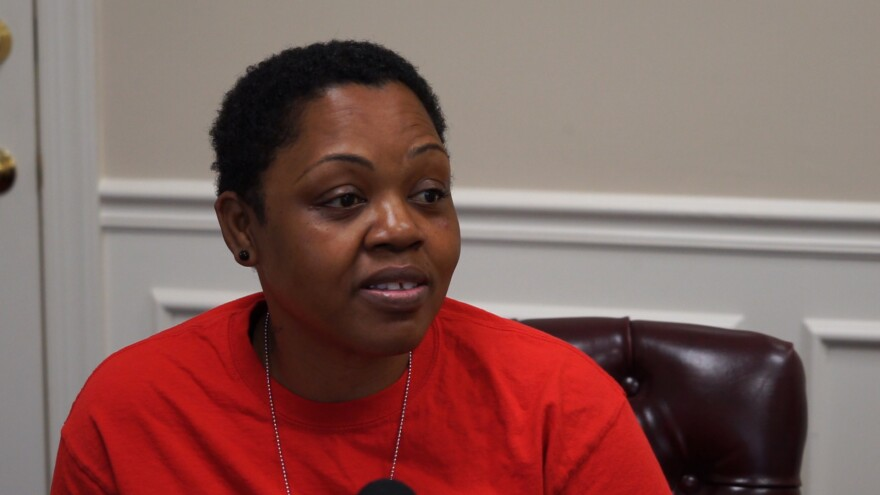A woman with short, black hair and a red shirt.