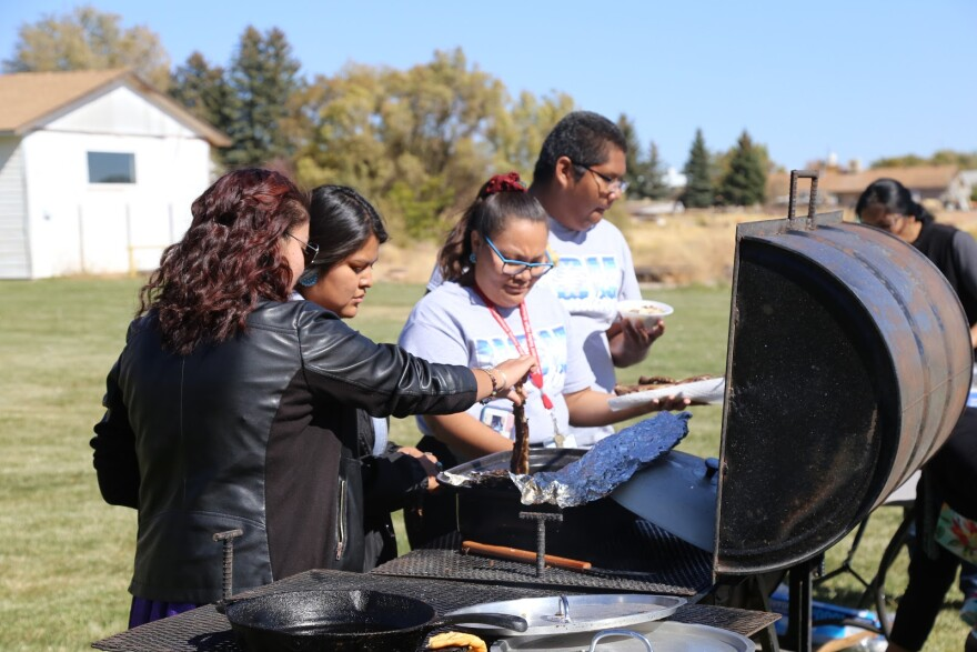 A photo of students taking mutton ribs off of a grill.