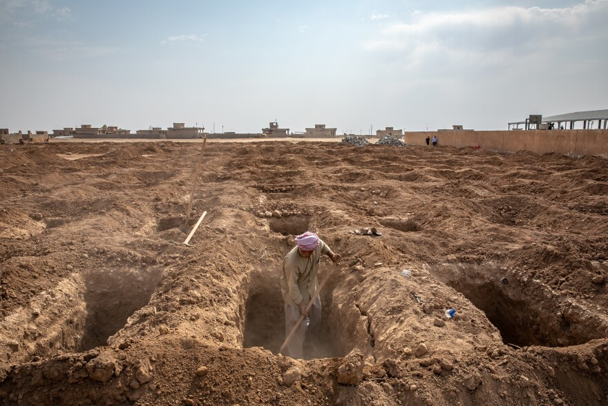 A man from a group of Yazidi survivors and volunteers digs new graves in 2019 to properly bury family members whose remains were discovered in mass graves in the Yazidi village of Kocho, northern Iraq. Now, a year later, many family members are still waiting for the bodies to undergo DNA testing and be returned to them.