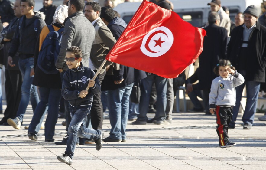 """<strong>December 2013:</strong> A Tunisian boy waves a flag as he runs at a rally in Tunis, marking the third anniversary of Tunisia's revolution. A prominent member of the group that's credited with averting civil war in the country says the group acted """"to give hope to young people."""""""