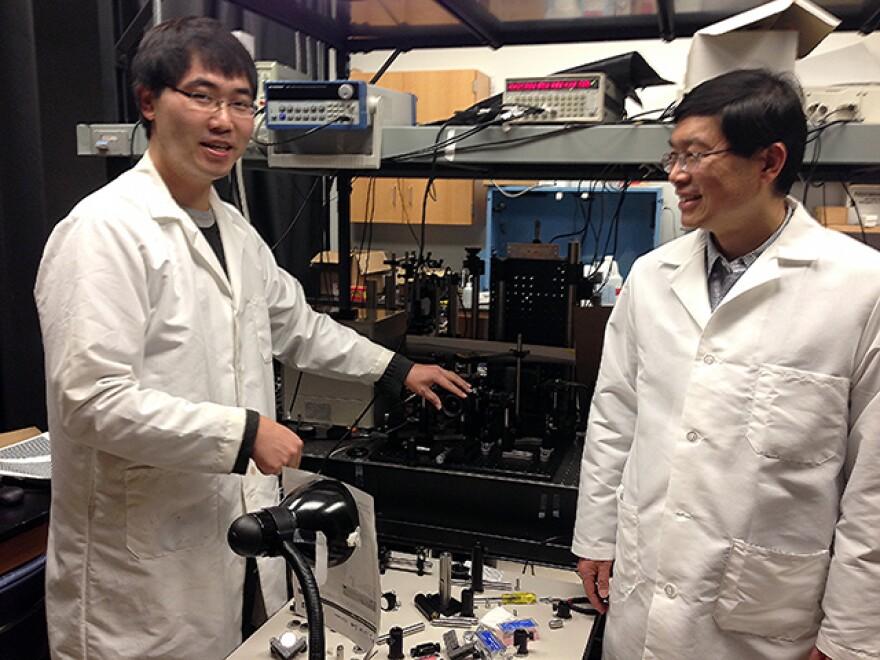 Washington University postdoctoral fellow Liang Gao (left) explains how the ultrafast camera works, as senior researcher Lihong Wang looks on.