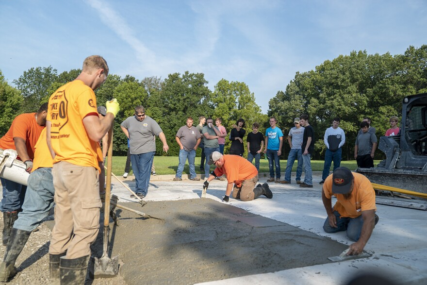 Edwardsville High School students observe labor apprentices pour concrete on Sept. 10. The high schoolers are part of a two year program where they learn aspects of the construction trade.