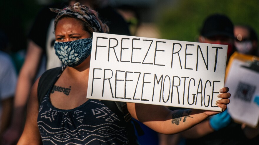 "A woman joins with other demonstrators during the ""Cancel Rent and Mortgages"" rally in late June in Minneapolis. The march was demanding the temporary cancellation of rents and mortgages as COVID-19 batters the economy."