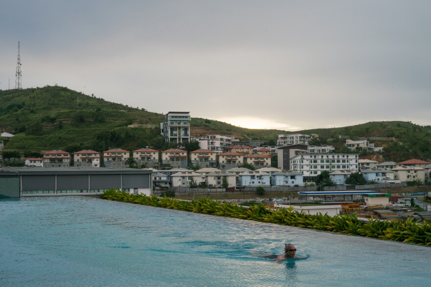 A woman swims in the pool at the Stanley Hotel And Suites, a luxury hotel in Port Moresby's upscale Waigani neighborhood, where many government buildings and a mega-mall are located.