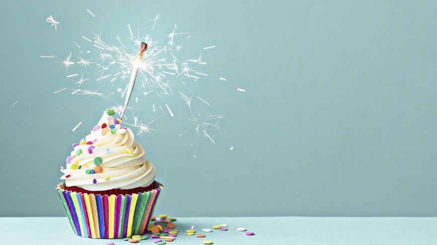 Cupcake decorated with colorful sprinkles and a sparkler.