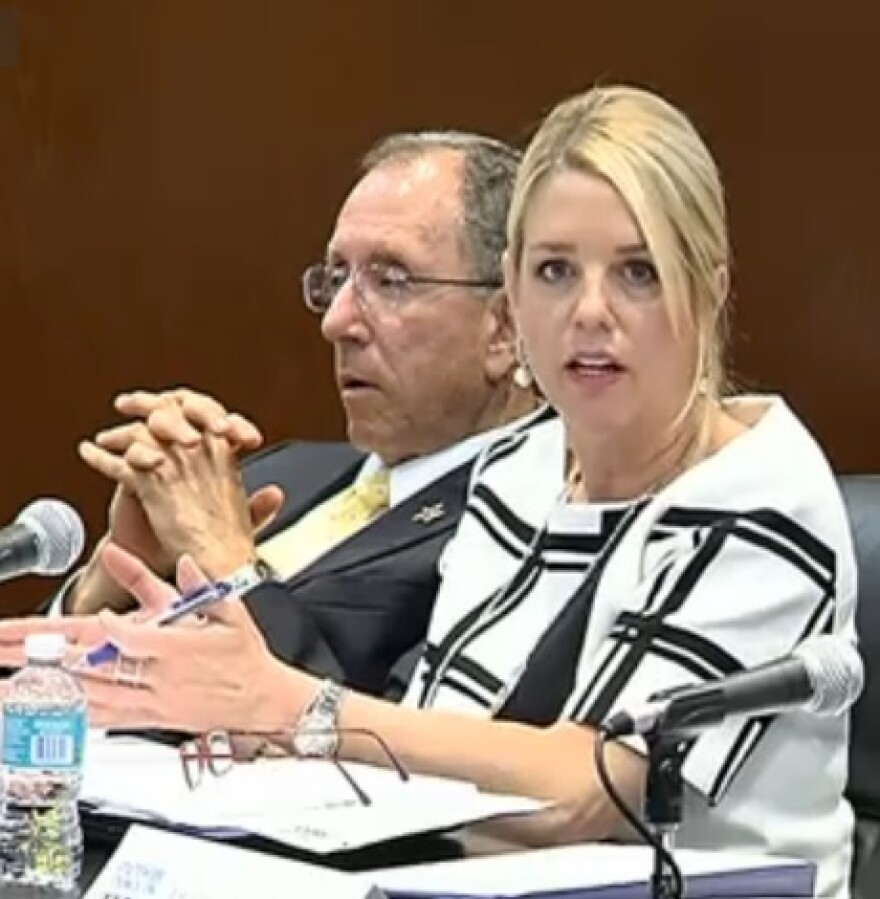 Florida Attorney General Pam Bondi speaking during Thursday's Statewide Council on Human Trafficking, while Martin County Sheriff William Snyder, among other panel members, listens.