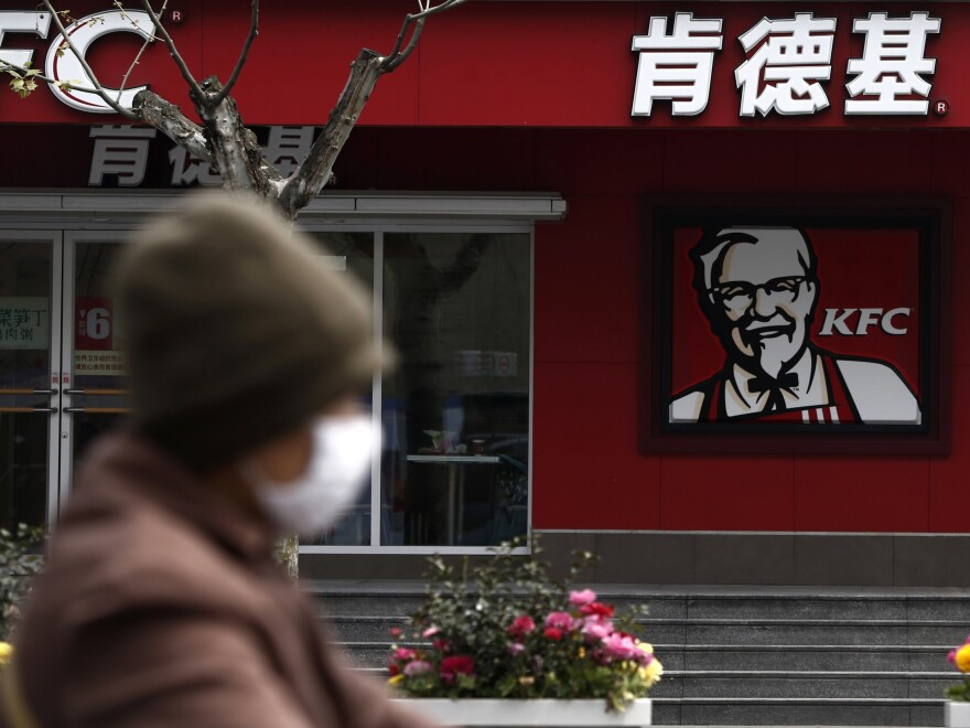 A woman wearing a mask rides past a KFC restaurant in Shanghai last month. Food scares and the bird flu haven't stopped many chicken lovers in the city from visiting KFC and other restaurants.