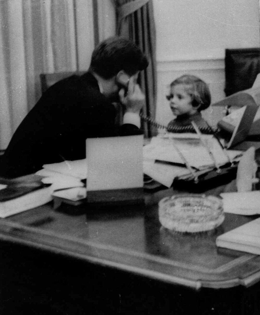 In this photo from March 1961, Kennedy talks on the phone with his wife, Jacqueline Kennedy, with their daughter, 3-year-old Caroline, at his side.