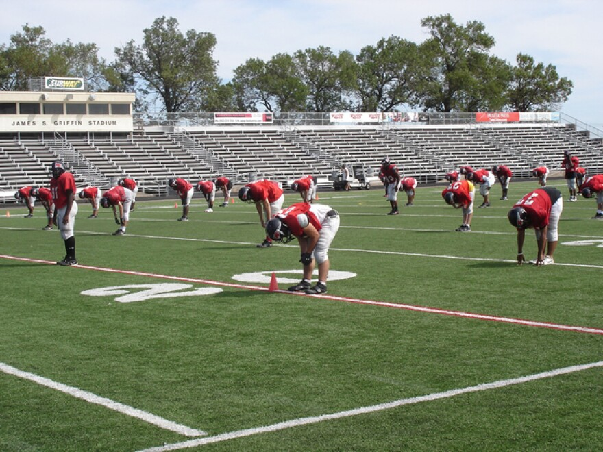 A football team practices on a field.